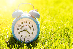 Summer vacation time - alarm clock in green grass Stock Photos