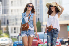 Summer vacation to beautiful women travelling by car. Two young women with suitcases. Vacation concept. Car trip. Summer vacation. Best friend posing with their Royalty Free Stock Photos