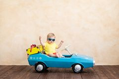 .Summer vacation and travel concept. Happy child riding toy vintage car. Funny kid playing at home. Summer vacation and travel concept stock photos