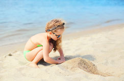 Summer vacation, travel concept - little girl child on beach playing Stock Photos