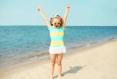 Summer vacation, travel concept - little girl child having fun on beach. Near sea Stock Photos