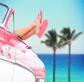 Summer vacation travel freedom concept. With cool convertible vintage car and woman feet out of window against tropical see background with palm trees. Girl Stock Photo