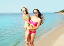 Summer vacation and travel - happy mother and child in swimsuit on beach Stock Photos