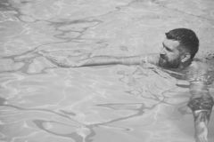 Summer vacation and travel to ocean. bearded man swimming in blue water. Relax in spa swimming pool, refreshment and stock images