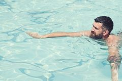 Summer vacation and travel to ocean. bearded man swimming in blue water. Relax in spa swimming pool, refreshment and royalty free stock photos