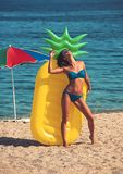 Summer vacation and travel to ocean. summer beach with woman sunbathing at yellow pineapple air mattress. Summer vacation and travel to ocean. summer beach with royalty free stock photo