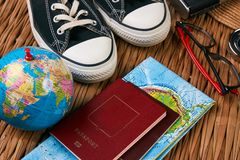 Summer vacation, travel, tourism and objects concept. Passport travel document photo camera sunglasses globe map, top view. Traveler items vacation travel Stock Image