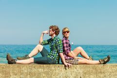 Hiking couple relaxing on sea coast. Summer vacation and traveling concept. Young hiking couple women men relaxing after hike on sea shore enjoying sunlight Stock Photography