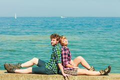 Hiking couple relaxing on sea coast. Summer vacation and traveling concept. Young hiking couple women men relaxing after hike on sea shore enjoying sunlight Stock Photo
