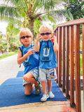 Two brothers in similar sunglasses and clothes at a tropical resort, Vietnam Royalty Free Stock Image