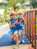 Two brothers in similar sunglasses and clothes at a tropical resort, Vietnam Royalty Free Stock Photos