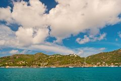 Summer vacation on tropical island. Mountain shore in blue sea on cloudy sky in gustavia, st.barts. Wild nature and. Environment, ecology. Holiday destination stock photography