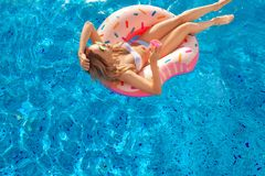 Summer Vacation. Woman in bikini on the inflatable donut mattress in the SPA swimming pool. Beach at the blue sea. Summer Vacation. Enjoying suntan Woman in royalty free stock photography