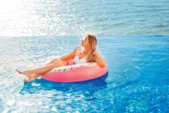 Summer Vacation. Woman in bikini on the inflatable donut mattress in the SPA swimming pool. Beach at the blue sea. Summer Vacation. Enjoying suntan Woman in royalty free stock image