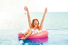 Summer Vacation. Woman in bikini on the inflatable donut mattress in the SPA swimming pool. Summer Vacation. Enjoying suntan Woman in bikini on the inflatable royalty free stock photography