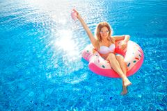 Summer Vacation. Woman in bikini on the inflatable donut mattress in the SPA swimming pool. Summer Vacation. Enjoying suntan Woman in bikini on the inflatable royalty free stock image