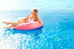 Summer Vacation. Woman in bikini on the inflatable donut mattress in the SPA swimming pool. Summer Vacation. Enjoying suntan Woman in bikini on the inflatable stock image