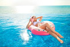 Summer Vacation. Woman in bikini on the inflatable donut mattress in the SPA swimming pool. Summer Vacation. Enjoying suntan Woman in bikini on the inflatable stock photography