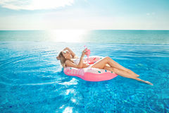 Summer Vacation. Woman in bikini on the inflatable donut mattress in the SPA swimming pool. Royalty Free Stock Photos