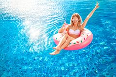 Summer Vacation. Woman in bikini on the inflatable donut mattress in the SPA swimming pool. Travel to the sea rest. Summer Vacation. Enjoying suntan Woman in stock images