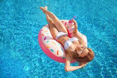 Summer Vacation. Woman in bikini on the inflatable donut mattress in the SPA swimming pool. Travel to the sea rest. Summer Vacation. Enjoying suntan Woman in stock photography