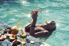 Summer vacation woman drink exotic tropical cocktail on beach with straw, sun tanned body, concept holiday travel. royalty free stock photo