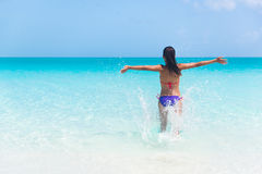 Summer vacation woman happy running in water beach. Summer vacation woman happy running into ocean on beach splaching water cheering full of joy and excitement Stock Photography