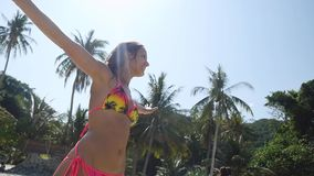 Summer vacation woman with straightened hands having fun on beach dances in the sun spinning around in slow motion. 1920x1080, hd stock footage