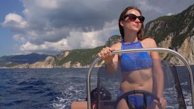 Summer vacation - young girl driving a motor boat on the sea. Slow motion stock footage