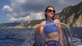 Summer vacation - young girl driving a motor boat on the sea stock footage