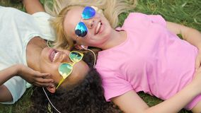 Summer vacation, young women lying on grass and listening to music on smartphone. Stock footage stock video footage