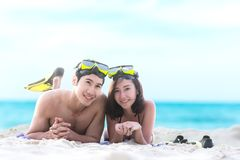 Summer Vacations. Beach travel couple having fun snorkeling. Asian smiling Couple lying and enjoy on summer beach sand with snorke royalty free stock image