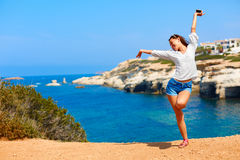 Summer vacations. Girl with hands up near the sea. Stock Photo