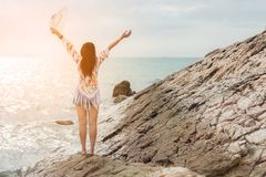 Summer Vacations.  Hppyy lifestyle and freedom woman on the beach with arms outstretched on the ocean seascape background, sunset Stock Images