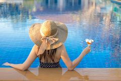 Summer Vacations. Lifestyle woman happy with bikini and big hat relaxing on the swimming pool, in holiday.