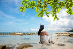 Summer Vacations. Lifestyle women relaxing and enjoying swing on the sand beach, fashion stunning stock photography
