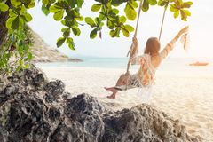 Summer Vacations.  Lifestyle women relaxing and enjoying swing on the sand beach, fashion stunning women on the tropical island so stock image