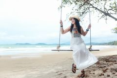 Summer Vacations. Lifestyle women relaxing and enjoying swing on the sand beach, fashion stunning women with white dress on the tr Stock Image