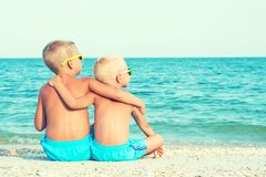 Two brothers relaxing on the beach,sitting on the sand and looking at the sea. Summer vacations. stock photos