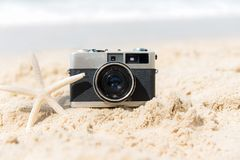 Summer Vacations. Vintage old camera of tourism on sandy beach with star fish. royalty free stock photography