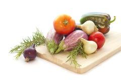 Summer veggies with wodden cutting board on white. Summer veggies tomates, eggplants, Onion on wooden cutting board isolated on white Royalty Free Stock Photos