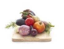Summer veggies with wodden cutting board on white. Summer veggies tomatoes, eggplants, Onion on wooden cutting board  on white Royalty Free Stock Images