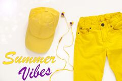 Yellow flatlay jeans, baseball cap and headphones on white background card,top view.Summer Vibes background