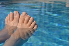 Summer vibes, feet in swimming pool, keeping cool royalty free stock photography