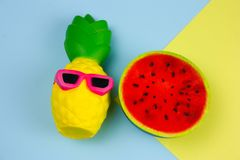 Free Summer Vibrant Blue And Yellow Background With Funny Pineapple Toy In Sunglasses And Squishy Toy Watermelon Stock Images - 139291394