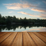Summer vibrant sunset reflected in calm lake waters with wooden Stock Image