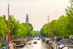 Summer view of an Amsterdam canal with people relaxing in small Royalty Free Stock Image