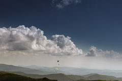 Summer view of Carpathian Mountains and Valleys, under blue sky with clouds. With pair of paragliders in sky. Stock Image