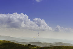 Summer view of Carpathian Mountains and Valleys, under blue sky with clouds. With pair of paragliders in sky. Royalty Free Stock Photos