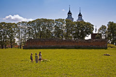 Summer view with children playing, church in the b Royalty Free Stock Photos